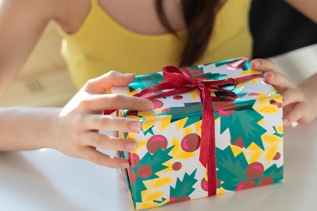 クリスマスプレゼント。女の子は贈り物で箱を開け、リボンをほどき、包装紙を取り除きます