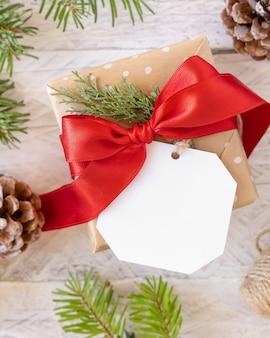 Рождественский подарок с пустой подарочной биркой, вид сверху, макет