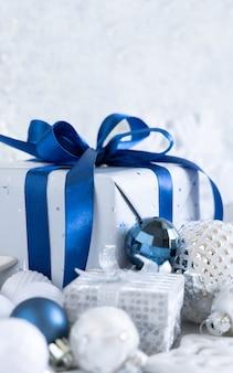 Рождественский подарок с синим бантом и серебряными украшениями крупным планом