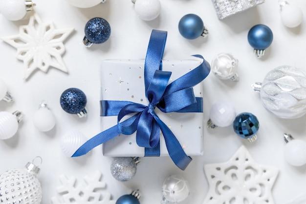 Рождественский подарок с синим бантом и серебряными украшениями, вид сверху