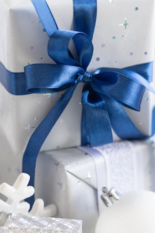Christmas present with blue bow and silver decorations closeup