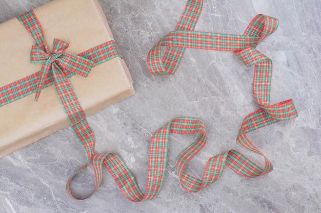Рождественский подарок с праздничным бантом на мраморном фоне.