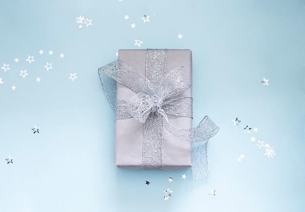 Рождественский подарок, обернутый серебряной лентой на голубом