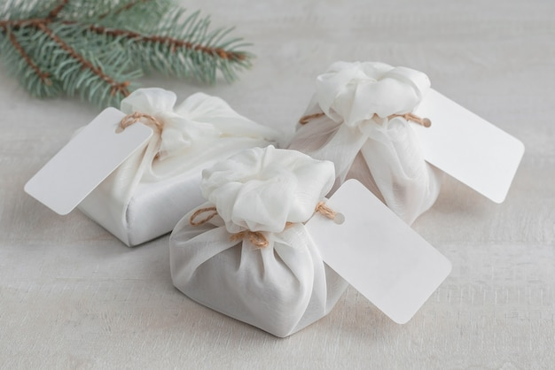 Christmas present wrapped with white furoshiki fabric with labels. eco friendly gift.