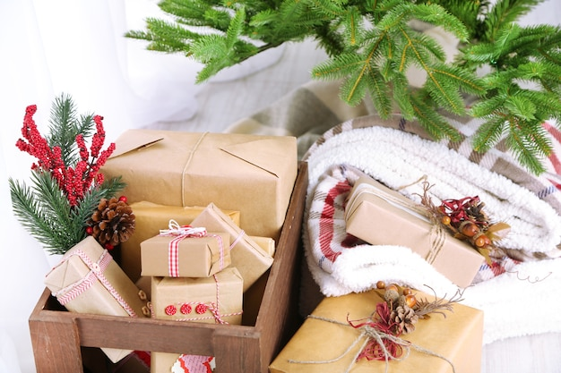 Рождественские подарки и украшения в коробках возле елки на светлой поверхности