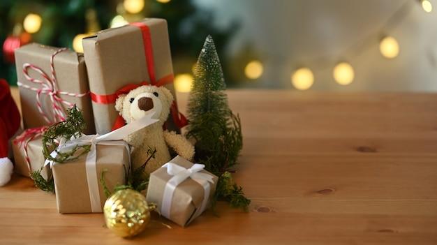 クリスマスプレゼントとテディベアが木製のテーブルに置かれました。