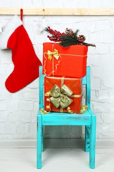 Christmas presents on blue chair on brick wall surface