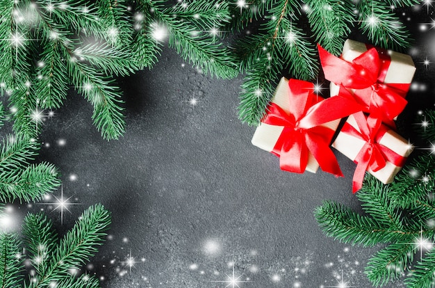 Christmas presents and fir tree on dark background.