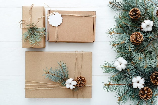 Christmas presents gifts boxes decorated with fir tree branches cotton on white background