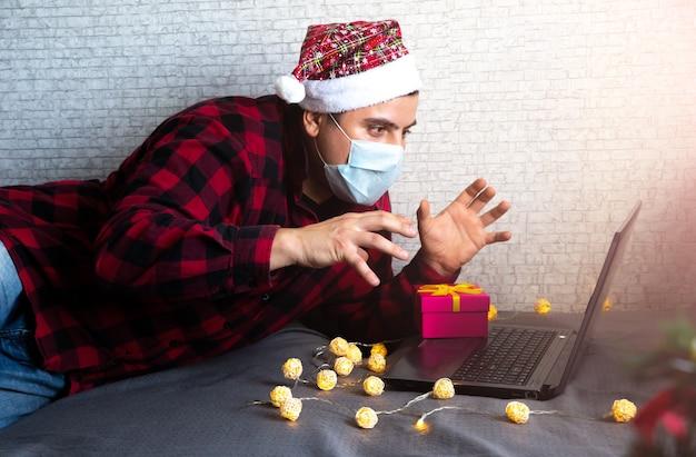 クリスマスプレゼントを贈ります。ビデオ通話を通じてボックスギフトを共有する医療マスクの男。単独で休日。新年のツリーと装飾が施されたライト。オンラインで祝う家族や友人。