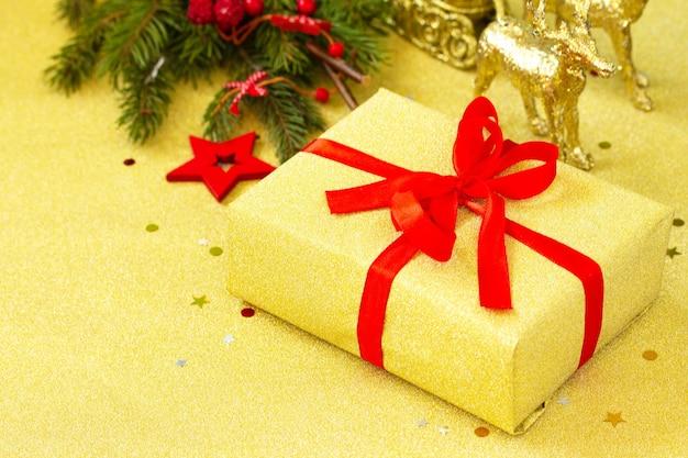 クリスマスプレゼント赤いリボンと木の枝の装飾が施された金色の箱コピースペース