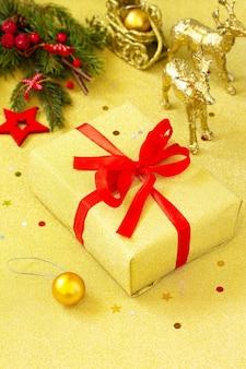クリスマスプレゼント赤いリボンと木の枝の装飾が施された金色の箱