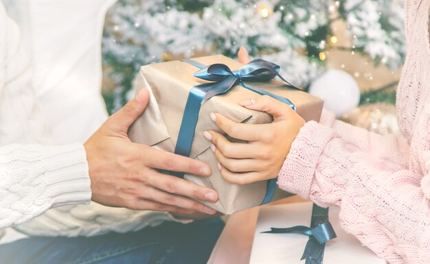 クリスマスは男性と女性の手に贈られます。ホリデー。セレクティブフォーカス。