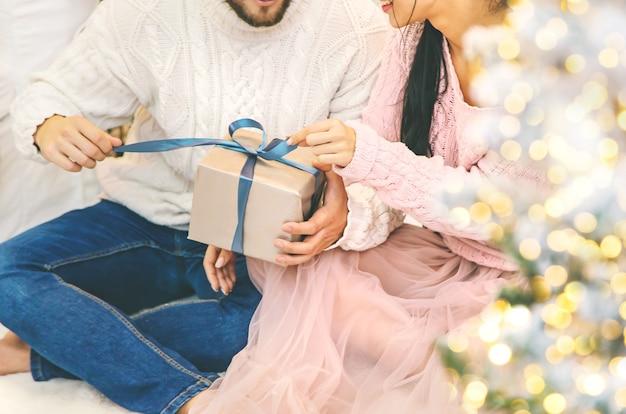 クリスマスは男性と女性の手に贈られます。セレクティブフォーカス。ホリデー。
