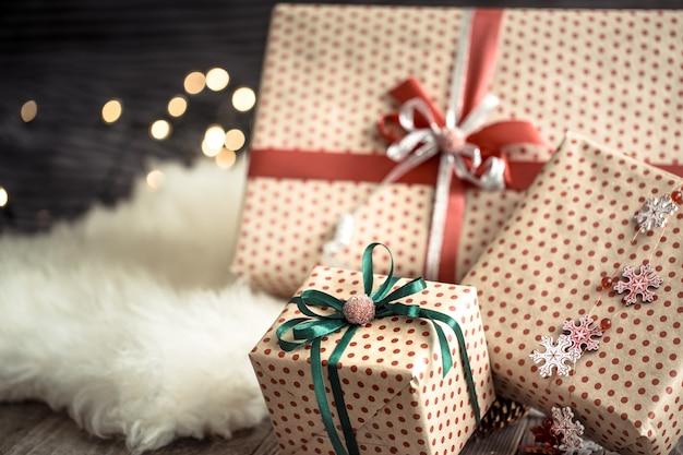 Regali di natale sopra le luci sulla parete scura sul tappeto accogliente. decorazioni natalizie