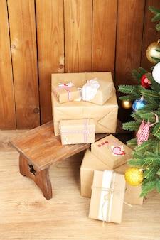 木製のテーブルの上のクリスマスツリーの近くにクリスマスプレゼント