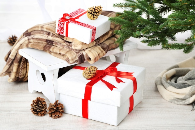Christmas presents  near christmas tree on wooden surface