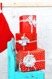 レンガの壁の青い椅子にクリスマスプレゼント