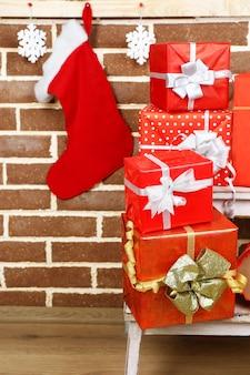 茶色のレンガの壁の表面のスタンドはしごにクリスマスプレゼント