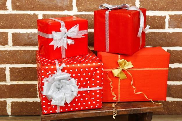 茶色のレンガの壁の背景のスツールにクリスマスプレゼント