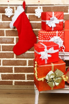 Christmas presents on stand ladder on brown brick wall surface
