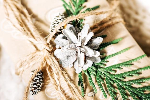 크리스마스 선물에는 면직물 배경에 소나무 콘과 잔가지로 장식된 선물 상자가 있으며 휴일을 준비합니다. 크리스마스 선물과 새해. 수제입니다.닫습니다. 선택적 초점
