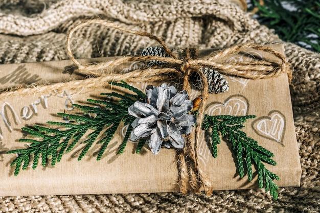 크리스마스 선물에는 면직물 배경에 소나무 콘과 잔가지로 장식된 선물 상자가 있으며 휴일을 준비합니다. 크리스마스 선물과 새해. 수공. 선택적 초점,