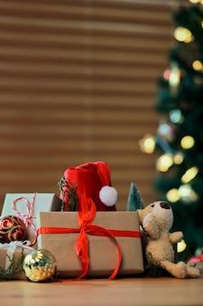 木製のテーブルに赤いリボン、サンタの帽子、テディベアのクリスマスプレゼント。