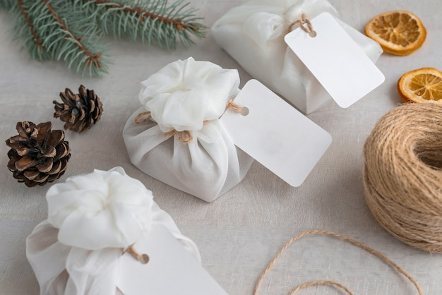 Christmas presents wrapped with white furoshiki fabric, labels and dried orange slices. eco friendly gift.