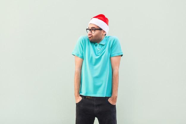 크리스마스 문제. 생각의 비행. 회색 벽에 서 있는 동안 멀리 바라보는 사려깊은 수염된 사업가. 스튜디오 촬영