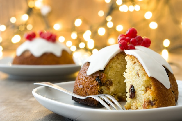 Christmas pudding on wooden table decorated with christmas light