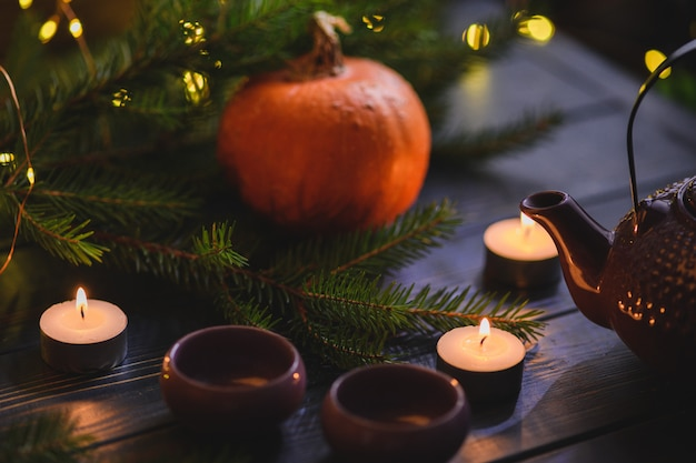 Christmas pumpkins on wooden table with lights