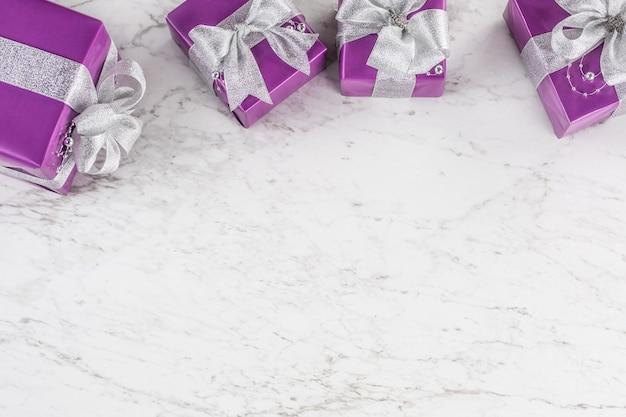 Рождественские фиолетовые подарки с серебряной лентой на белом мраморном столе.
