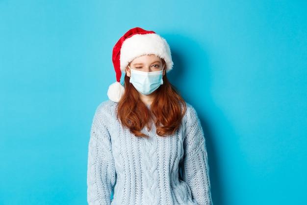 クリスマス、検疫、covid-19のコンセプト。フェイスマスクとサンタ帽子の生意気な赤毛の女性モデル、カメラでウィンク、陽気なクリスマスを願って、青い背景の上に立っています。