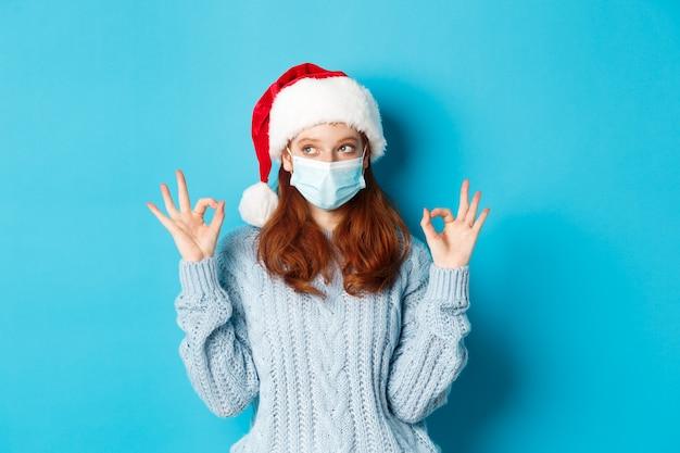 크리스마스, 검역 및 covid-19 개념입니다. 산타 모자와 스웨터를 입은 귀여운 10대 빨간 머리 소녀, 코로나바이러스의 얼굴 마스크를 쓰고, 괜찮은 표시를 보여주고, 승인하고, 무언가를 칭찬합니다.