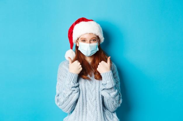 Concetto di natale, quarantena e covid-19. carina ragazza dai capelli rossi con cappello e maglione da babbo natale, con indosso una maschera da coronavirus, che mostra i pollici in su, in piedi su sfondo blu