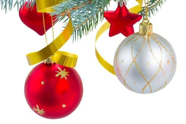 白い背景で隔離のモミの木にぶら下がっているクリスマスの赤と銀のボール