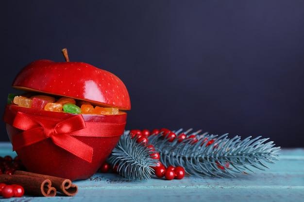 カラーの木製テーブルと暗い背景にドライフルーツを詰めたクリスマスの赤いリンゴ