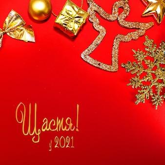 クリスマスの赤い背景の金の装飾新年ウクライナ語テキスト幸福グリーティングカード