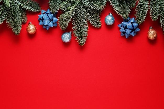 Рождественский красный фон с елкой, шарами и бантом