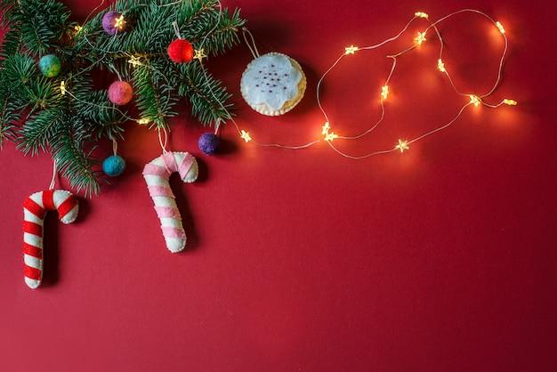 手作りのクリスマスオーナメントで飾られたクリスマスツリーの枝のあるクリスマスの赤いbakckground:フェルトキャンディケインとコピースペースのあるクリスマスボールブ