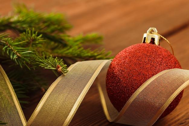 모피 나무 가지 나무 배경 가운데 크리스마스 빨간 공과 황금 리본