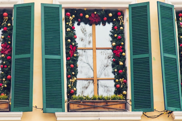 Christmas red ball decorated windows on vintage house.