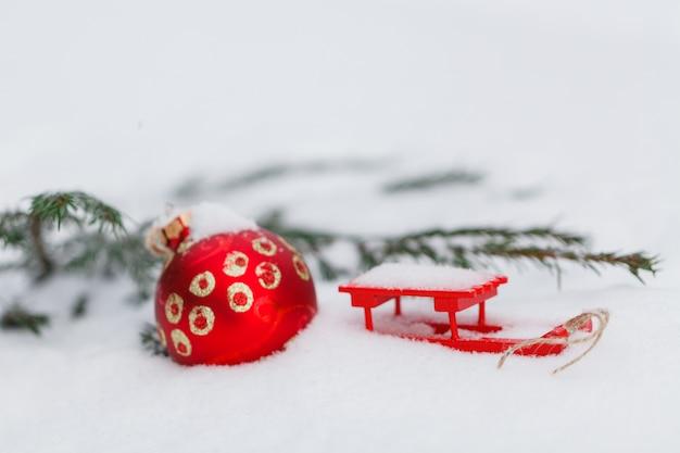 雪に覆われたモミの枝にぶら下がっている赤いクリスマスボール