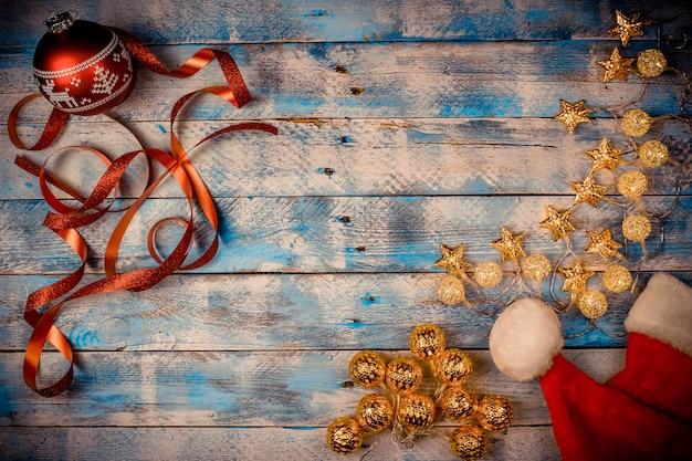 赤いクリスマスボール、サンタ帽子、素朴なヴィンテージの木製の背景にリボンとクリスマスライト。