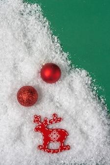 コピースペースと緑の背景に雪の中でクリスマスの赤いボールと鹿の置物。上面図。
