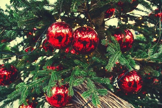 クリスマスツリーにぶら下がっているクリスマスの赤いボールコピースペースとクリスマスツリーの背景