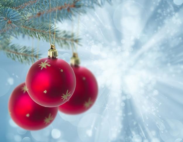 Рождественские красные шары, висящие на елке на синем боке, фон