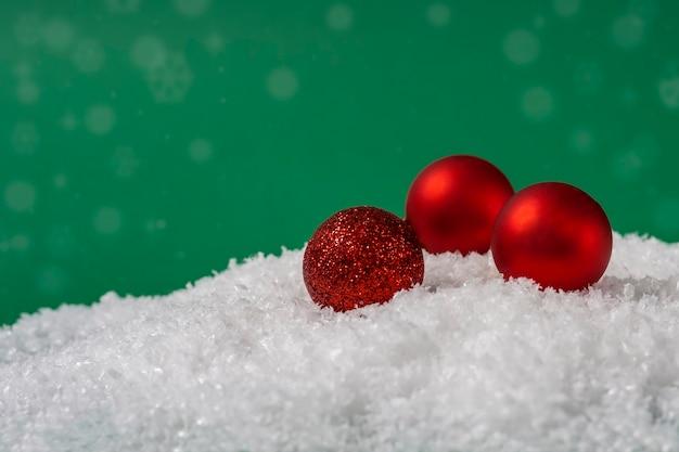 コピースペースと緑の背景に雪の中でクリスマスの赤いボール。