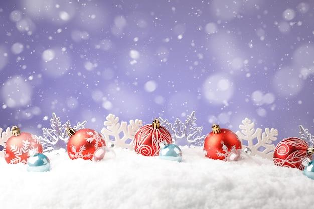 보라색 배경에 눈송이와 빨간색 크리스마스 볼